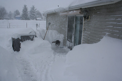 Mitch's dog house is totaly covered in snow. So is the B-B-Q.