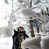 Israel Cerda, of Boulder, sweeps off the snow from the roof of Rocky Mountain Chocolate Factory on the Pearl Street Mall in the midst of a winter storm that was expected to drop near a foot of snow throughout the day Friday, March 19, 2010.  <br /> <br /> KASIA BROUSSALIAN