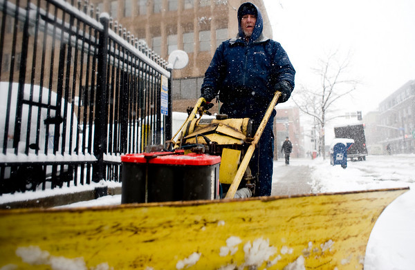 Larry Wagoner, an employee of the downtown U.S. Post Office, brushes snow fro the sidewalk in the midst of a winter storm that was expected to drop near a foot of snow throughout the day Friday, March 19, 2010.  <br /> <br /> KASIA BROUSSALIAN