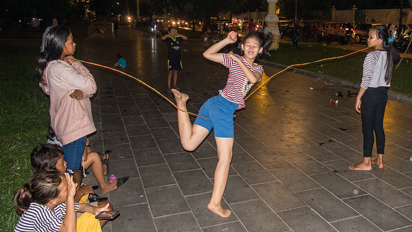 Young women enjoying a form of jump rope made from rubber bands in the park.  Phnom Penh, Cambodia