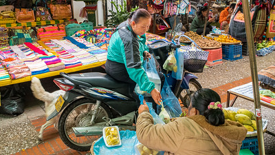"""Buying your fruit and vegetables off the saddle of your motor scooter adds a new dimension to """"drive through"""" in Luang Prabang."""