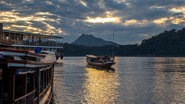 "A ""slow boat""  makes it's way up the Mekong River in Luang Prabang at sunset."