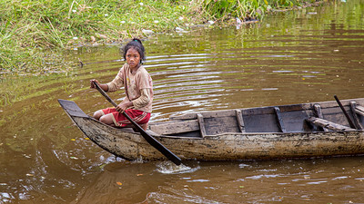 A young woman paddling her canoe along the canals of Beng Mealea, Angkor