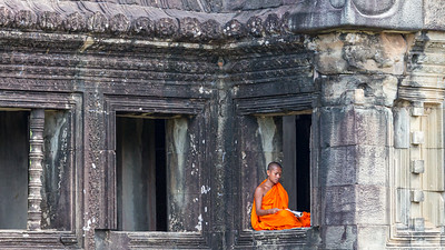 A Buddhist monk finds repose among the ruins of Angkor Wat.