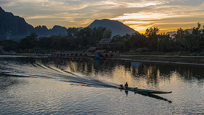 A long tail boat makes its way up the Nam Song River while the sun sets over Vang Vieng.