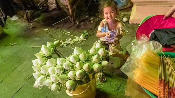A young girl helping her mother sell lotus flowers on the bank of the Mekong River, Phnom Penh, Cambodia.
