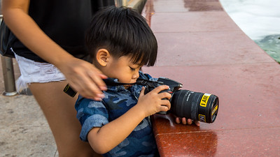My that's a big lens for a small photographer.  This young man is getting an early start in his photography career.  I believe lesson one involves taking the lens cap off.  Vientiane, Laos
