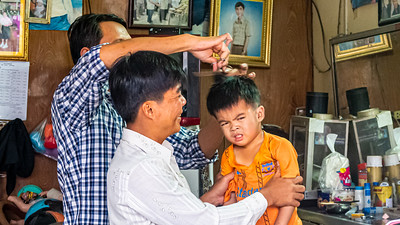 Everyone is having a good time except the young guy in the chair.  A trip to the barber in Cambodia can be a very traumatic event.