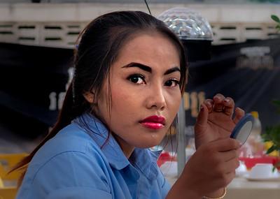 A waitress prepares for her evening shift at a Phnom Penh restaurant.