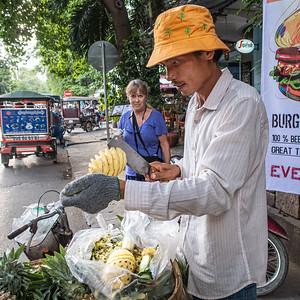 Linda watches a pineapple vendor prepare our tropical treat.  Phnom Penh.
