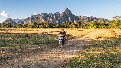 A back roads motor bike rider makes his way through the karst backed rice fields outside Vang Vieng