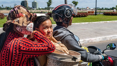 Helmets not required.  A family makes their way home from the Phnom Penh market.