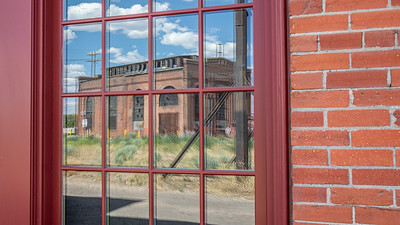 The old power house for the Southern Pacific Railroad yards is reflected in the windows of the roundhouse in Evanston, Wyoming. Now a National Historic Park is was part of the original transcontinental railroad finished in 1869.