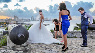 The newly married groom stands waiting as his wife is attended to for their wedding photos.  The sun setting over Havana provided a stunning backdrop for a wedding at Fortaleza de San Carlos.  It was a beautiful finish for our journey to Cuba.