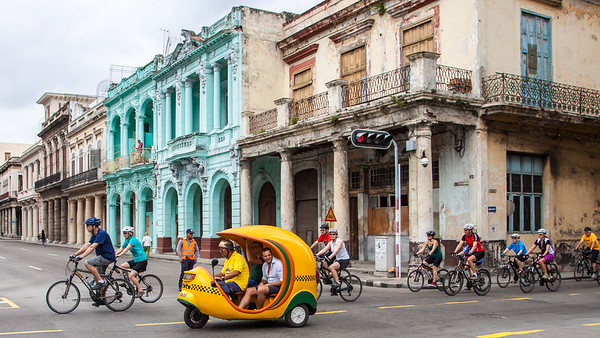 "A ""Coco"" makes its way past a bicycle tour group in Old Havana."