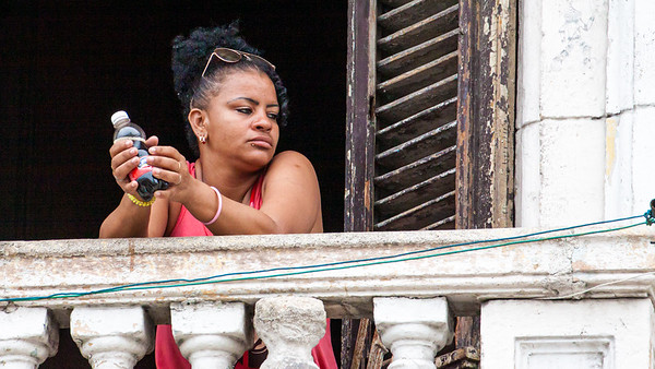 A woman watching the world go by from her balcony in Havana.