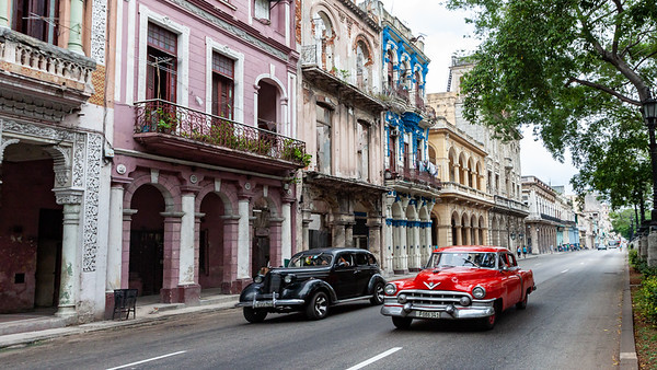 "A pair of classic automobiles cruising ""El Prado"" in Havana."