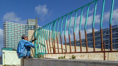 A Havanan spruces up a railing with a new coat of paint along the Malecon