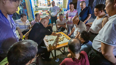 A friendly neighborhood game of Xiangqi (elephant chess). How it is played I have no idea.  Two players moved the pieces while 13 onlookers kibitzed and shouted out their opinions as to what the next move should be. A very spirited game played in the back alleys of the neighborhood.