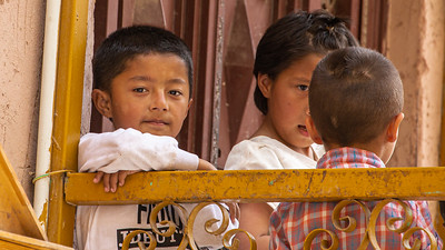 This young Uyghur boy is watching the world go by from his balcony in Kashgar.