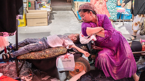 Merchants or shoppers I couldn't decide which. For this mother and her son this seemed to be the spot for a nap.  Sunday Market in Kashgar, Western China