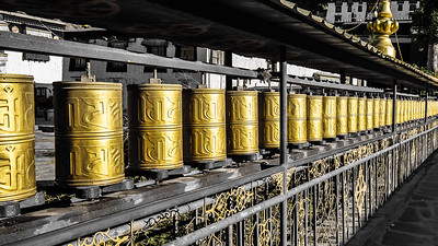 Prayer wheels at the Pelkor Chode Monastery.in Gyantse.  Typically they are inscribed with the prayer Om MaNi PadMe Hum which symbolizes the six realms of existence, Generosity, Ethics, Patience, Diligence, Renunciation and Wisdom. Turned in a clockwise direction it helps the devote achieve purification and accumulate good karma.