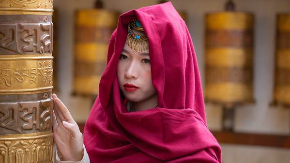 """It is very popular with the Chinese to be photographed """"on location"""" dressed in exotic attire.  I captured this image of a woman posing near the prayer wheels on Barkhor Street."""