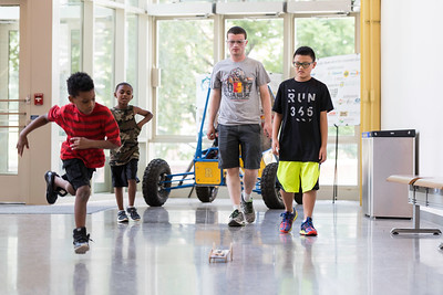 l-r: Javon Byron, Michael Hayes, Gilead Biggie (UR ME, '18), and Porter Hermon test a mousetrap car in Rettner Hall. // Student participants in Horizons at Warner, a six-week summer enrichment program that engages K–8 Rochester City School District students at University of Rochester's Warner School of Education are pictured August 3, 2017.  // photo by J. Adam Fenster / University of Rochester