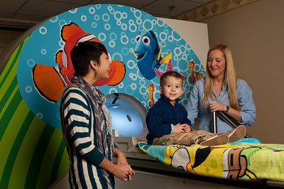 University of Rochester Brain & Cognitive Sciences Research Assistants Courtney Lussier [R] and Vy Vo talk with Mason Ray, 4 of Penfield, NY as he lies on a decommissioned MRI machine January 30, 2013. Researchers use the device to acclimate children to a working fMRI device used to create brain scans for studies examining how children's brains change as they develop intellectual abilities like reading and math. // photo by J. Adam Fenster / University of Rochester