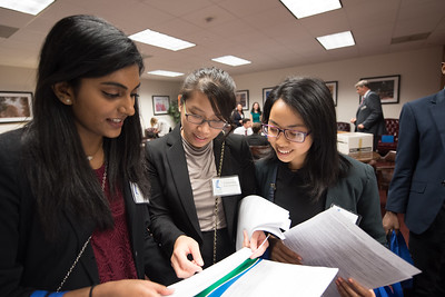 Saumya Thomas (left), Charoenrat Kaewmanorom, and Tran Tran plan out their routes through the capitol.