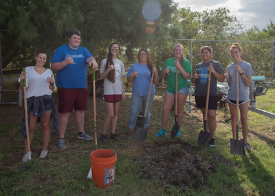 Students take a break from planting a fruit tree to take a group photo.
