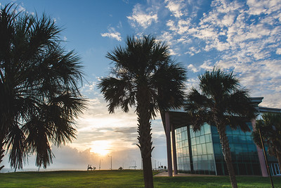 The Performing Arts Center reflects the sun's rays peaking out over the clouds on the horizon, setting up for a beautiful sunrise on campus.