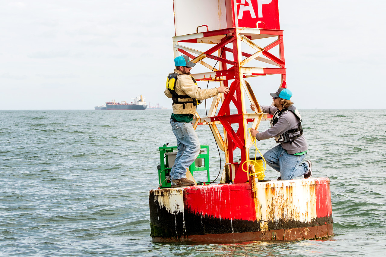 TAMU-CC Conrad Blucher Institute research engineers Zachary Hasdorff (left), and Alistair Lord attach prepare to tie a rope to the buoy during a CCPORTS module installation off of the coast  ...