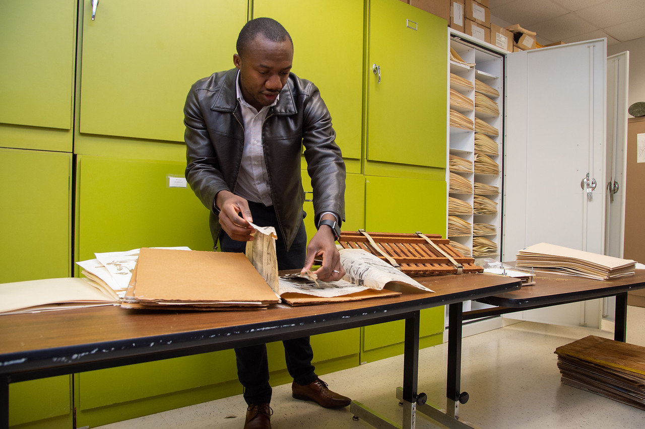 Barnabas Daru showing the process to properly archive  a plant.