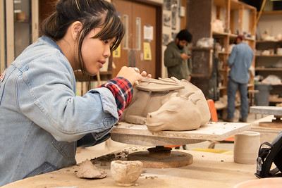 Nichole Schiller working on her ceramic dragon in the Center for the Arts building.