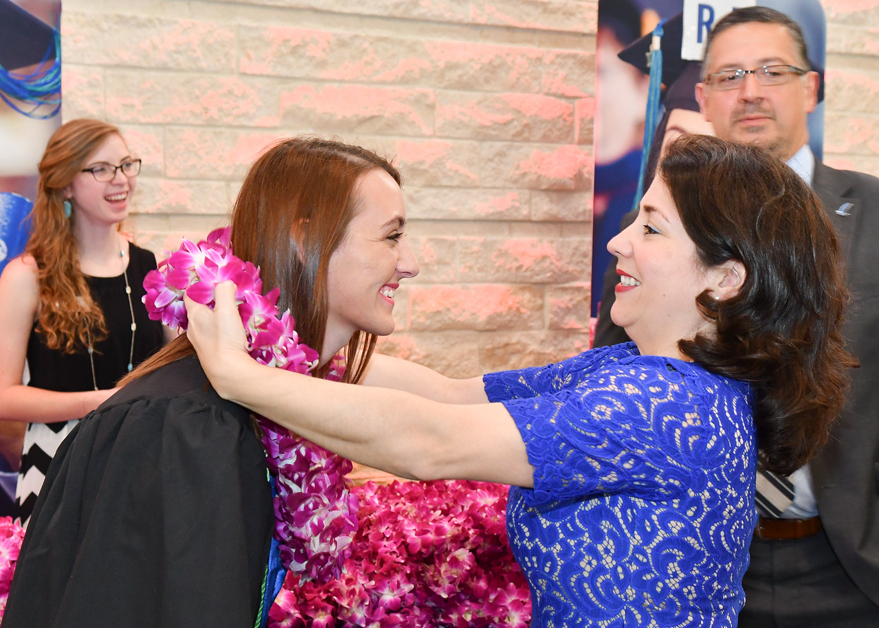 Environmental Science major Bailey Moehl (left) receives her lei from Peggy Lara before the Spring 2018 Commencement ceremony on May 12, 2018.