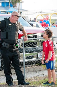 An Aransas Pass police officer interacts with a young citizen.