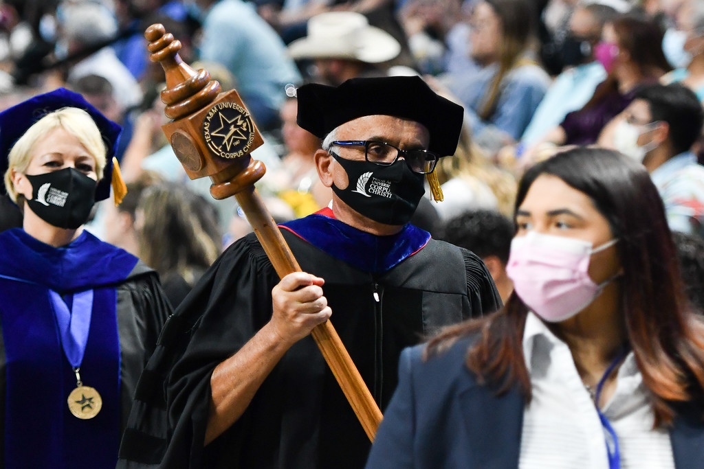 Dr. Kamiar Kouzekanani carries the mace as the summer 2021 commencement ceremony procession begins at the American Bank Center.