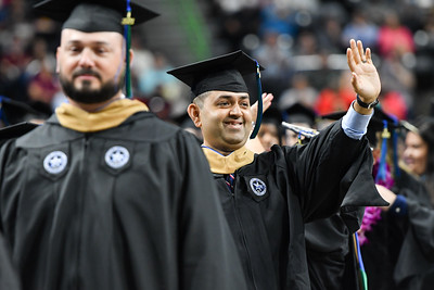 An Islander graduate waves to family, friends, and supporters during the summer 2021 commencement ceremony.