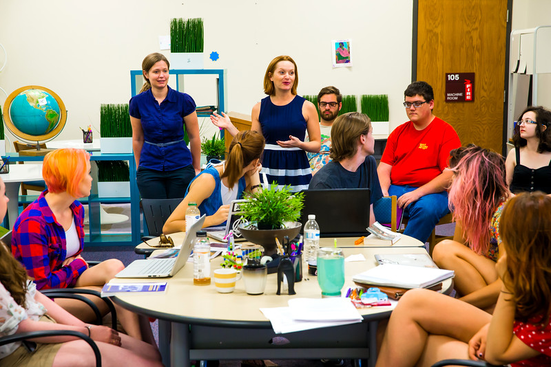 Director of Writing Jennifer Wells talks to students in the Writing Resource Center.
