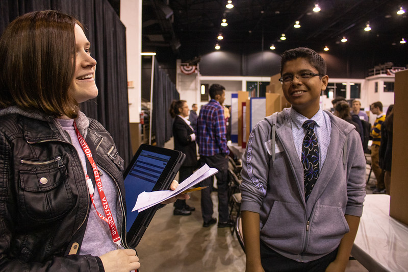 Marina Mangie, admissions marketing coordinator at New College, talks with Marcos Bautista, a ninth-grader at Suncoast Polytechnical High School in Sarasota about his STEM Fair project, that compared the effectiveness of a popular weed killer with nontoxic alternatives.