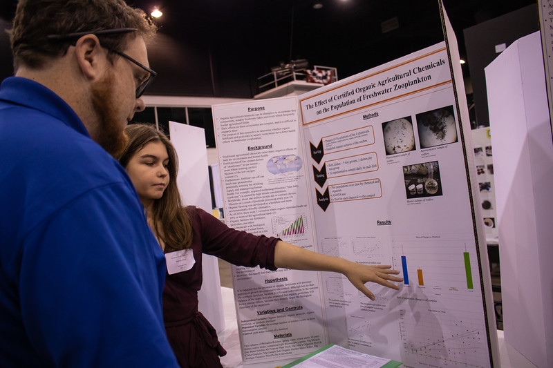 New College's Travis Hardin judges Sarasota High student Elizabeth Abbott's project at the Sarasota County STEM Fair Jan. 30 at Robarts Arena.