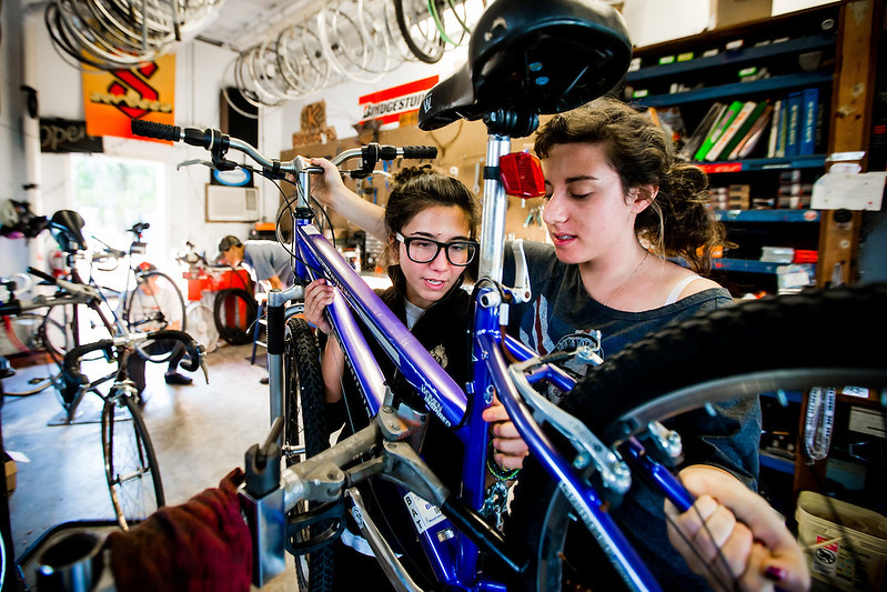 Second-year student Kaithleen Conoepan, left, a Bike Shoppe volunteer, helps fourth-year student Jade Sheinwald repair her bike.