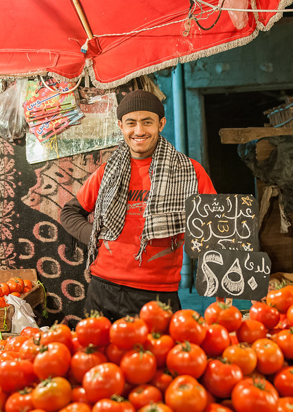 "Ahmed, was happy to wear his favorite soccer team color ""Al Ahly"" watching the game while selling red tomatoes under red tent umbrella."