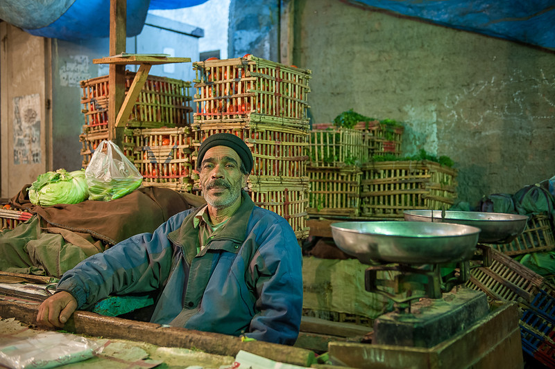 setting next to his old style scale, Abd El Razik, is selling plastic bags and weighting vegetables to neighboring vendors.