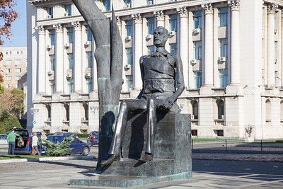 This modern sculpture graces a small square in Bucharest, Romania.  The building behind the sculpture is notable because when the Romanian dictator Nicolae Ceausescu attempted to flee the country in 1989, he boarded a helicopter on the roof of this building. He was unable to escape the country and was captured and executed.