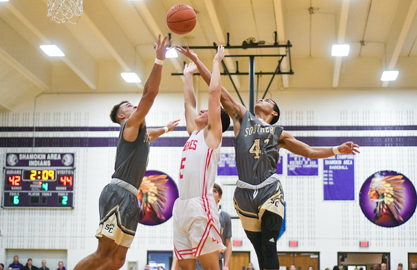 Southern Columbia's Julian Fleming and Damian Ares go for a rebound against Lourdes Regional's Jacob Rees during Thursday night's game in Shamokin.