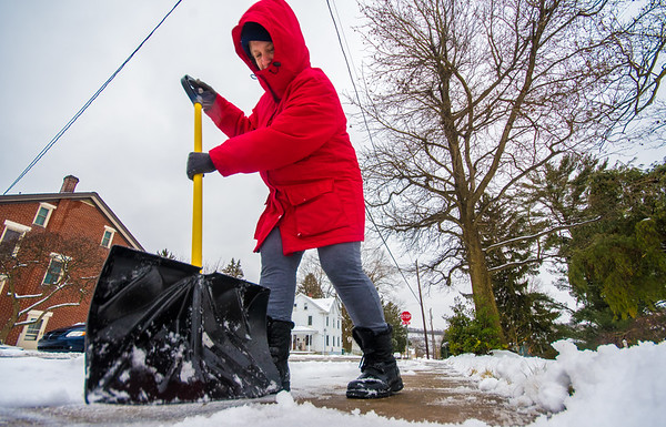 Wendy Lloyd, of Northumberland, shovels her mother-in-law's sidewalk in Northumberland on Tuesday afternoon.