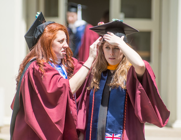 Nickala Hagarty, of West Chester, helps Casey Falkenstein, of Downington, with her cap before the start of Susquehanna University's graduation program on Wednesday.