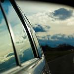 Side mirror pov of car, curvy highway, and storm sky, I-90, WA USA